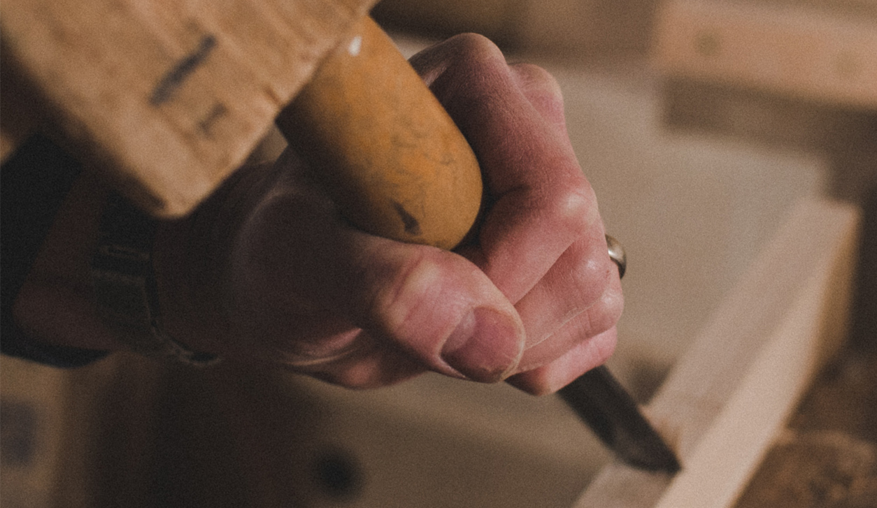 Charlie Caffyn's hands chiselling wood. A new way to buy furniture.